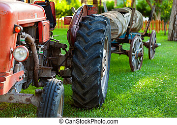 Old vintage farm tractor with cart