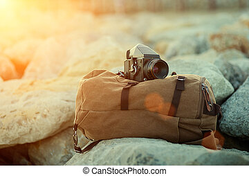 old vintage film medium format camera lies on the stones against the backdrop of a canvas vintage backpack