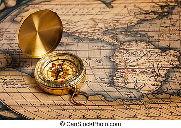 Old vintage golden compass on ancient map