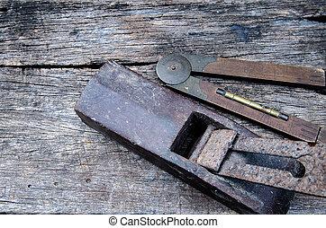 old vintage hand tools on wood background (plane and gauge)