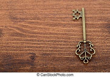 Old vintage key on a wooden background.
