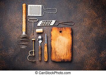 Old vintage kitchen utensils on rusty background