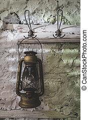 Old vintage lantern lamp on painted stone wall.