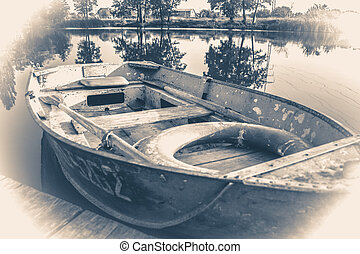 Old vintage photo. A few old simple boats on the wooden pier