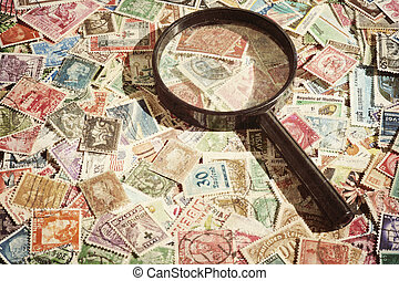 Old vintage postage stamps and magnifying glass, grunge...