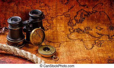 Old vintage retro compass and spyglass on ancient world map...