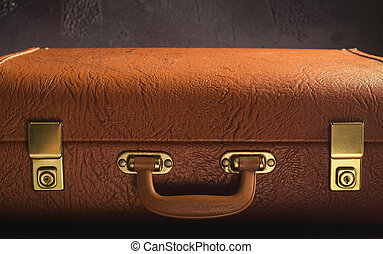 Old vintage, retro leather suitcase on dark background. Front view, toned