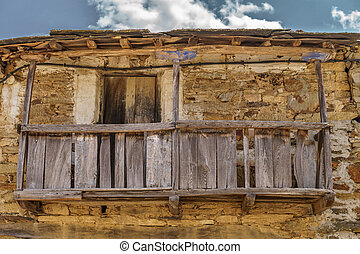 Old vintage run-down wooden balcony, stone facade - Front...