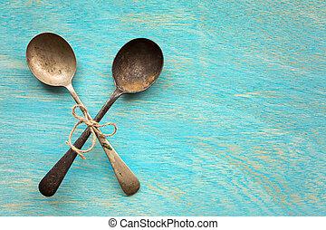 Old vintage spoons on blue wooden background
