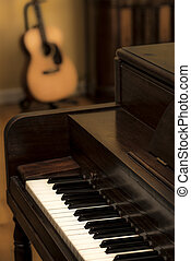 Old vintage upright wooden piano with keys in forground and acoustic guitar and antique radio in background, warm, sepia color