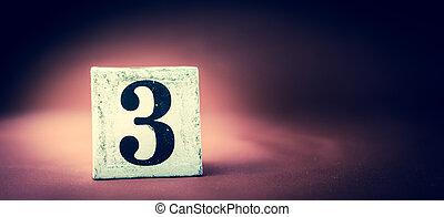 Old vintage wooden block with digit 3, number three - vivid maroon background