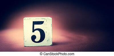 Old vintage wooden block with digit 5, number five - vivid maroon background