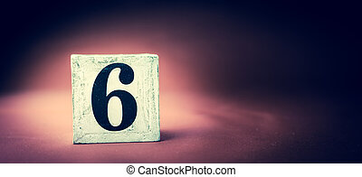 Old vintage wooden block with digit 6, number six - vivid maroon background