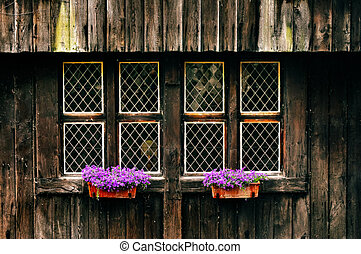 Old vintage wooden wall with rusty windows and flowers