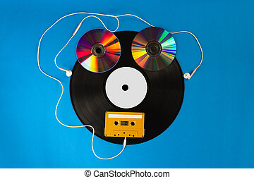 Old vinyl records and CD with audio cassette tape create shape a robot and Ear Headphones on blue background