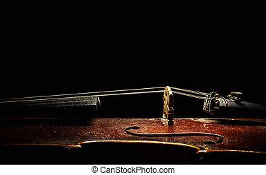 Details of an old dusty violin on black background, view from aside.