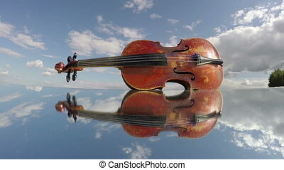 old used violin music instrument on mirror in space and clouds motion. Art concept, timelapse 4K