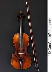 Old violin with bow on black background