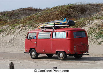 Old volkswagen bus with surfboards on the beach