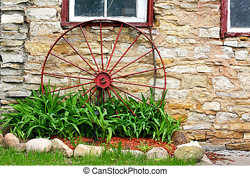 Old Wagon Wheel in Front of Stone Barn