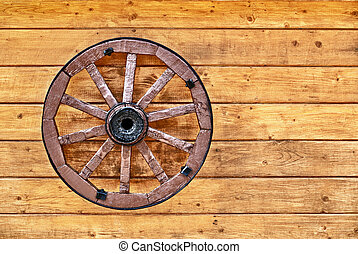 Old wagon wheel on a wooden wall
