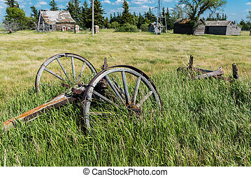 Old wagon wheels in an abandoned prairie yard with an old farmhouse, wind mill, and bins in the background