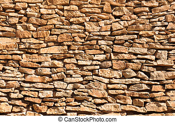 old wall made of big and little yellow stones - yellow...