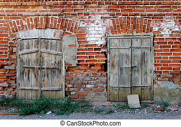 Old wall of red brick with two closed windows