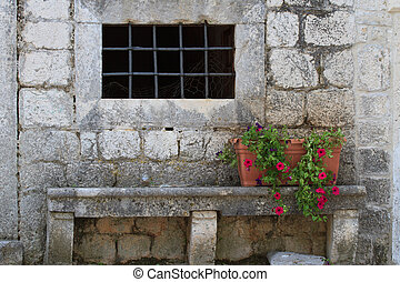 Old wall of the house with a window and a bench with flower