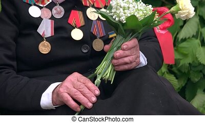 Old war veteran with flowers and medals. 9 may, victory day....