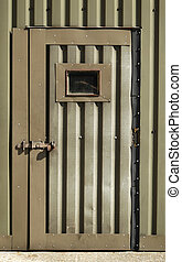 old wartime door - battered metal door of an old military...