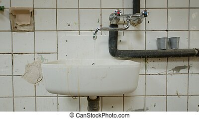 Old wash basin on tiled wall leaking water