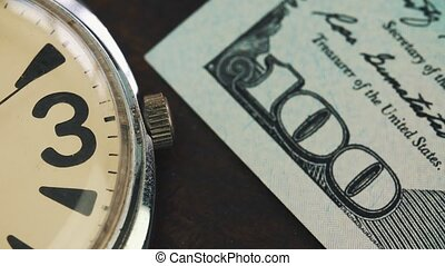 Old watch lies on the table on onde hundred dollar banknote