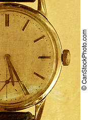 Old watch on a gold grunge background