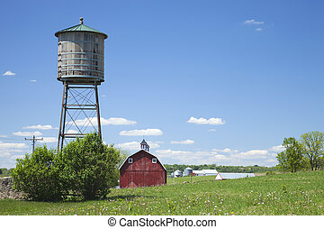 Old water cistern and red barn in rural Iowa