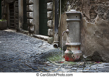 Old water tap in an alleyway in Rome, Italy