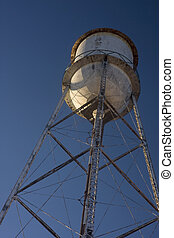 old water tower against blue sky
