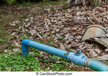Old water valve with blue plastic pipe in garden