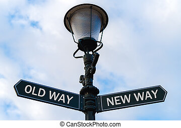 Old Way versus New Way directional signs on guidepost -...