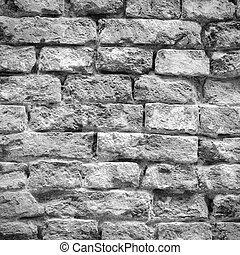 Old weathered and battered brick wall texture in black and white