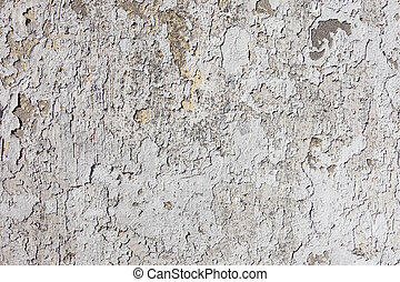 Old weathered flaky white paint on a wall.