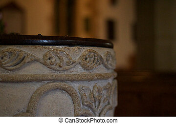 Old weathered font in ancient Christian church with space for copy
