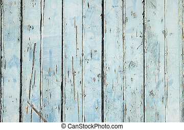 Old weathered light blue painted fence close up.