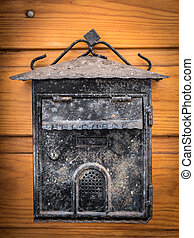 Old weathered mailbox hanging on a wooden door
