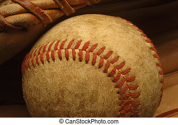 Old well-worn Baseball in a glove. - A close-up of a...