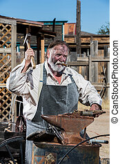 Male Blacksmith in Old West Swings Hammer at Anvil