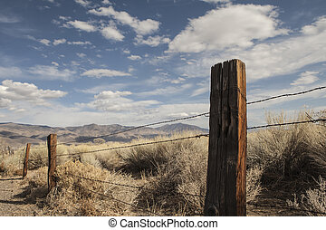 Fence post with barbed wire fencing in high desert of the west with blue sky and puffy clouds.