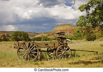 Old West wooden wagon/ cart in green grass against a mountain backdrop and blue sky with copy space.