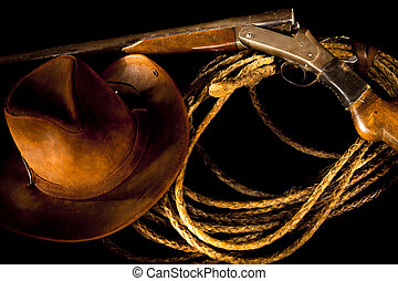 Old Western still life with gun, rope and cowboy hat on a dark background.