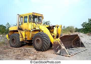 Old wheel loader bulldozer with bucket standing in sandpit...